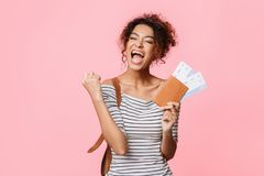Overjoyed woman with tickets screaming, clenching fist like winner. Pink background stock photography