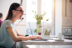 Overjoyed woman working on the laptop. Full of joy. Joyful beautiful smiling woman sitting at the table and expressing gladness while working on the laptop royalty free stock image