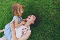 Overjoyed woman in light dress and little cute child baby girl lie on green grass in park rest play and have fun. Mother. Overjoyed women in light dress and stock photography