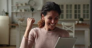 Overjoyed young caucasian woman celebrating online lottery win.