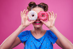 Overjoyed young girl peeking through two sprinkled donutnuts. Close-up of overjoyed young girl peeking through two sprinkled donutnuts isolated over pink Royalty Free Stock Photos