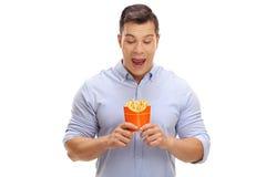 Overjoyed young man looking at a bag of fries Stock Photos