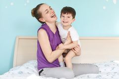 Overjoyed young mother and son smile joyfully, have fun together, sit on comfortable bed in bedroom, wait for father from work, ha. Ve good relationships. Family royalty free stock photography