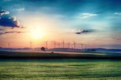 Overklig morgonsoluppgång på fälten med vindturbiner i bakgrunden Royaltyfri Foto