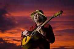 overklig utomhus- solnedgång för gitarrist royaltyfri bild