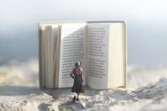 Overkligt ögonblick av en kvinna som går in mot en jätte- bok royaltyfria foton