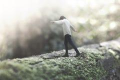 Overkligt ögonblick av gå för kvinna som är allsidigt på en jätte- trädstam i skogen arkivbild