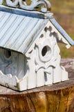 Overladen lichtblauw en wit vogelhuis op boomstomp Stock Foto's