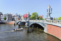 Overladen oude brug met een boot in Amsterdam Stock Foto