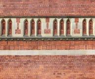 Overladen rode die bakstenen muur met complexe patronen en de gotische decoratieve boog die van de stijlsteen op een groot oud ge royalty-vrije stock foto