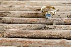Overladen verlovingsring op een patroon met natuurlijke houten die stokken, lijnenpatroon van natuurlijke houten stokken wordt ge stock foto