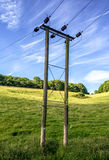 Overland Electricity Cable with Poles. A complete view of overland electricity poles and cables, running across the countryside, through farmland and supplying Royalty Free Stock Photo