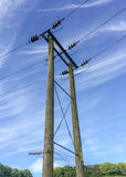 Overland Electricity Cable with Poles. A view of overland electricity poles and cables, running across the countryside, through farmland and supplying power to Royalty Free Stock Image