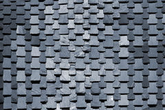 Overlapping stone slabs on a roof. Tiled shingle background Stock Image