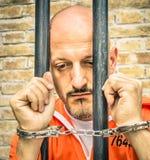 Overledene die - Droevige Gevangene met Handcuffs achter de tralies lopen Stock Afbeeldingen