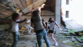 Overleefde vrouw die met een kanon in de verlaten bouw lopen die aanval van zombieën vermijden stock footage