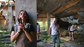 Overleefde vrouw met een kanon die achter een kolom van zombieën in de verlaten bouw verbergen stock video