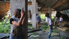Overleefde vrouw met een kanon die achter een kolom van zombieën in de verlaten bouw verbergen Een haar opmerken en zombie die lo stock videobeelden