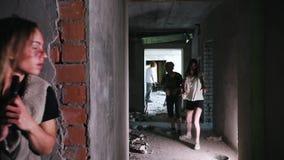 Overleefde vrouw terwijl de zombieapocalyps met een kanon die achter een muur van de zombieën verbergen stock video