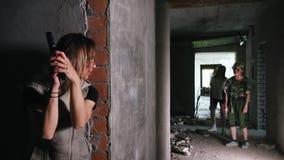 Overleefde vrouw terwijl de zombieapocalyps met een kanon die achter een muur verbergen en de zombieën bekijken stock footage