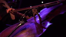Overleg, een hand die van de vrouwenmusicus de cello op stadium het spelen, overhandigt dicht omhoog stock video