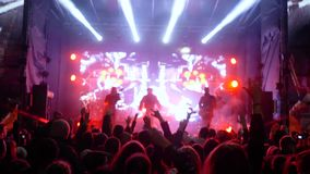 Overleg van levende muziek, menigte van ventilators die in ritme bij rotsfestival springen in verlichting stock videobeelden