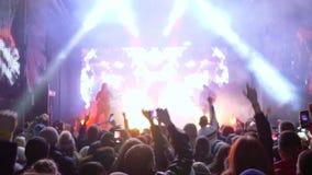 Overlegpartij, menigte die van ventilators in ritme bij rotsfestival springen met telefoons in handen stock footage