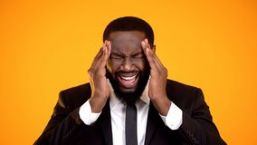Overloaded african-american man suffering headache, shouting and rubbing temples royalty free stock photo