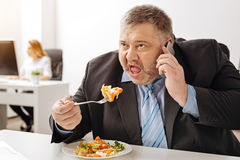 Overloaded ambitious employee cannot have a proper meal. Yes, I am still listening. Hungry worried corpulent guy answering a phone call in the middle of having a Stock Photos