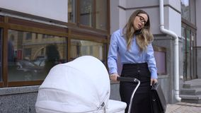 Overloaded business mother talking phone and swinging infant carriage, balance. Stock footage stock video footage