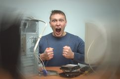 Computer repairman. Computer technician engineer. Support service. Overloaded computer repairman keeps a screwdrivers in his hands and screams. Computer Royalty Free Stock Photo