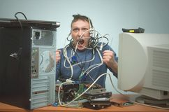 Computer repairman. Computer technician engineer. Support service. Overloaded computer repairman tired from his work and goes crazy. Computer technician. PC Royalty Free Stock Photo