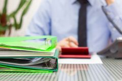 Overloaded consultant in blur with stack of binders and speaking. On phone Stock Photo