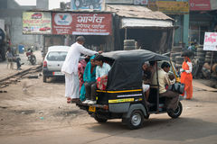 Overloaded indian tuk tuk on typical messy street, India. AGRA, INDIA - NOVEMBER 15: Overloaded by people indian tuk tuk on typical messy street in central India Stock Photo