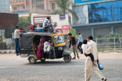 Overloaded indian tuk tuk on typical messy street, India Stock Images