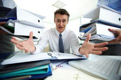 Overloaded with paperwork. Desperate businessman not knowing what to do with all paperwork Royalty Free Stock Photo