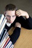 Overloaded Student Looking At Pile of Books Stock Photography