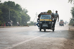 Overloaded and tuk-tuks motorcycles on covered by haze route, Ce Royalty Free Stock Image