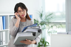 Overloaded at work. Asian female entrepreneur wit many folders talking on phone Stock Photography