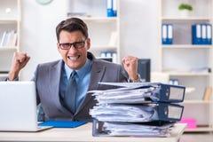 The overloaded with work employee under paperwork burden Stock Photo