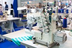 Overlock machine, nobody, clothing sew on fabric. Factory production, cloth manufacturing, needlework technology Stock Photography