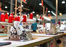 Overlock machine on sewing factory, nobody. Clothing sew. Textile fabric.  Cloth manufacturing, needlework technology Royalty Free Stock Photography