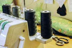 Overlock standing on the table with spools of thread in black. royalty free stock images