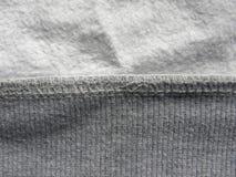 Overlock stitch. On gray cotton fabric royalty free stock photos