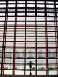 Overlook. Young girl looking through the glass curtain wall of Zhengzhou International Conference & Exhibition Center stock images