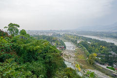 Overlook to riverside city from mountaintop in cloudy foggy wint Royalty Free Stock Photography