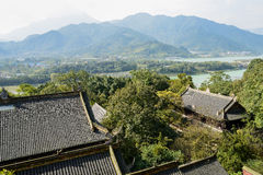 Overlooking ancient Chinese buildings in woods near river on sun Stock Images