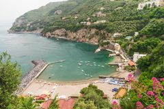 A bay on the coast at Vico Equense, Italy. Overlooking a bay on the Amalfi coast at Vico Equense, near Sorrento, Italy with a harbour, moored boats and beach Royalty Free Stock Image