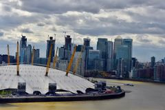 The O2 Arena Thames river and London cityscape. Overlooking the dome of  the O2 arena by the Thames river bank and canary wharf skyline in London UK stock photos