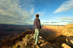 Overlooking Grand Canyon. Male tourist overlooking the Grand Canyon at sunset royalty free stock photos